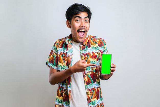 Junger gutaussehender asiatischer mann mit grünem bildschirm des smartphones auf weißem, isoliertem hintergrund sehr glücklich, der mit hand und finger zur seite zeigt