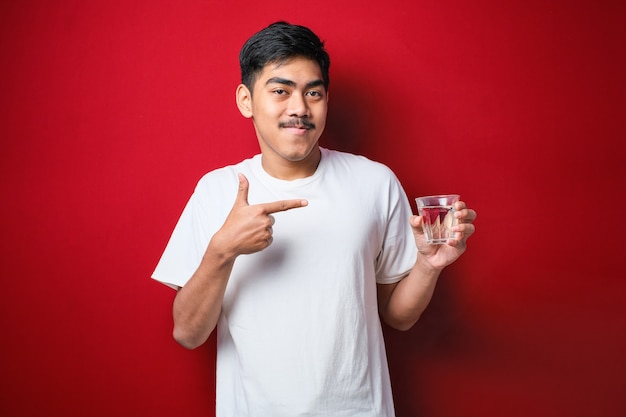 Junger gutaussehender asiatischer mann mit weißem t-shirt, der ein glas wasser trinkt und den daumen nach oben zur seite zeigt, lächelt glücklich mit offenem mund über rotem hintergrund Premium Fotos