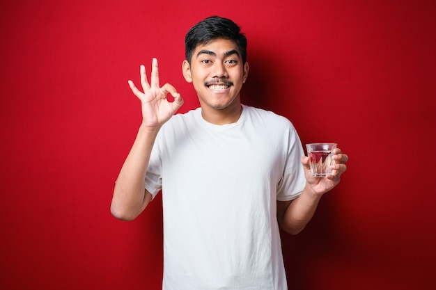 Junger gutaussehender asiatischer mann mit weißem t-shirt, der ein glas wasser trinkt und den daumen nach oben zur seite zeigt, lächelt glücklich mit offenem mund über rotem hintergrund