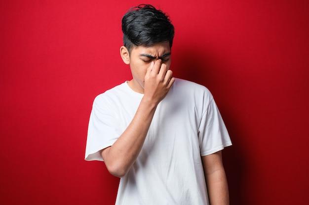 Junger gutaussehender asiatischer mann mit weißem t-shirt, der über isoliertem rotem hintergrund steht, mit der hand auf dem kopf für schmerzen im kopf, weil stress. migräne leiden.