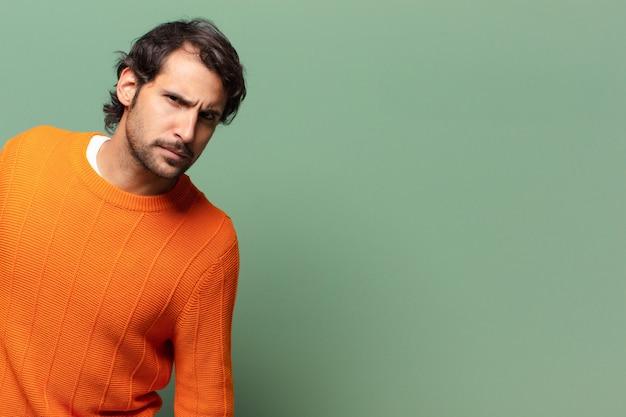 Junger gutaussehender ausdrucksvoller und wütender indischer mann mit einem kopierraum copy