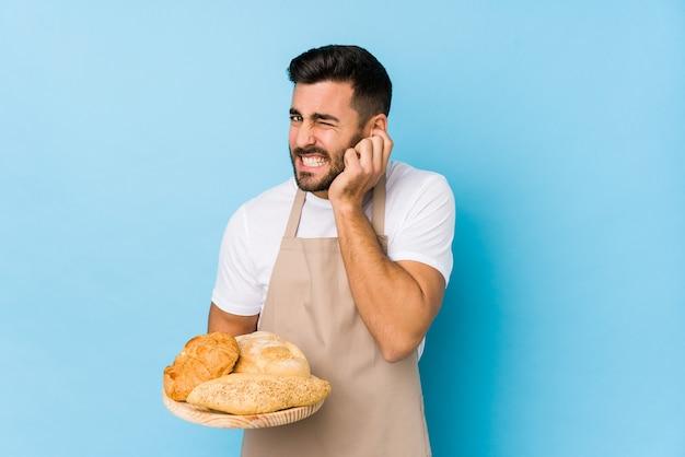 Junger gutaussehender bäckermann isoliert, der ohren mit händen bedeckt.