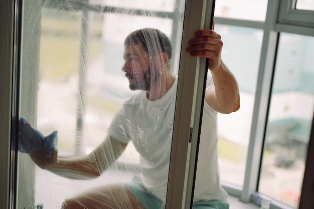 Junger gutaussehender bärtiger mann macht frühjahrsputz in einer gemütlichen wohnung, die fenster mit tuch wäscht