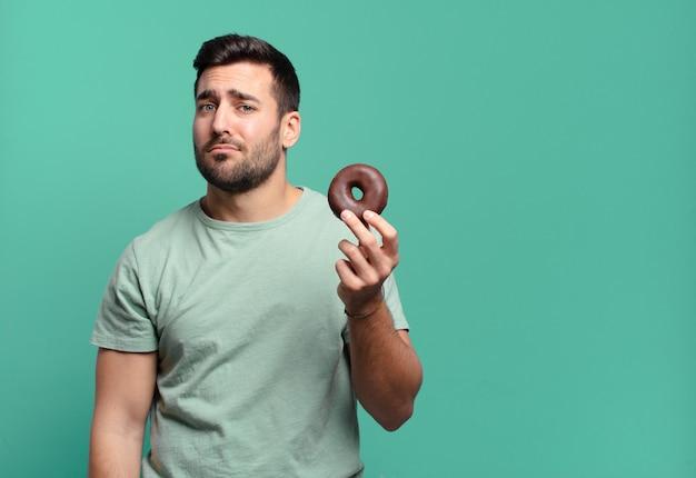 Junger gutaussehender blonder mann mit einem schokoladenkrapfenfrühstückskonzept