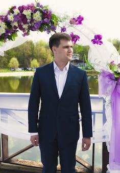 Junger gutaussehender bräutigam, der bei der zeremonie auf die braut unter blumenbogen wartet