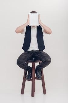 Junger gutaussehender brünetter mann mit bart in weißem hemd und schwarzer weste, der eine tablette vor seinem gesicht auf grauem hintergrund hält