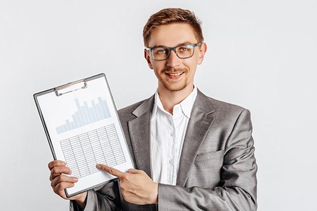 Junger gutaussehender brunet-mann in gläsern lächelt und zeigt auf dokumente auf weiß lokalisiert