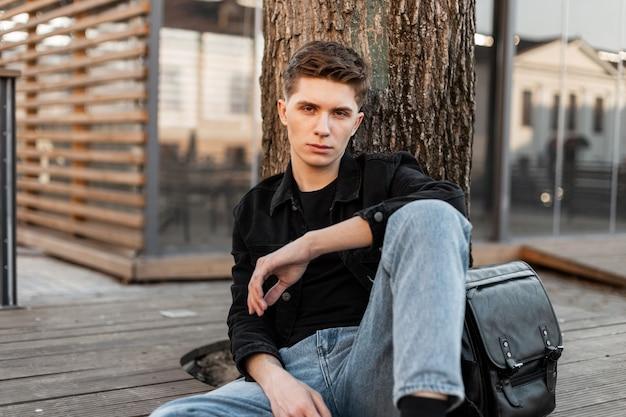 Junger gutaussehender englischer mann mit frisur in jeanskleidung