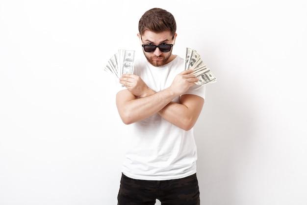 Junger gutaussehender ernster mann mit bart in einem weißen hemd, das viele hundert-dollar-scheine hält. geld