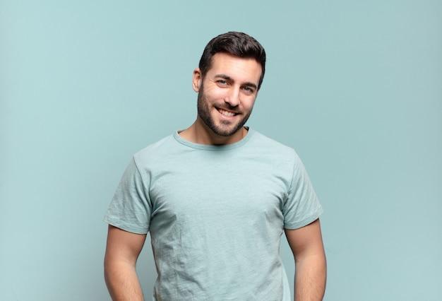 Junger gutaussehender erwachsener mann, der fröhlich und beiläufig mit einem positiven, glücklichen, selbstbewussten und entspannten ausdruck lächelt