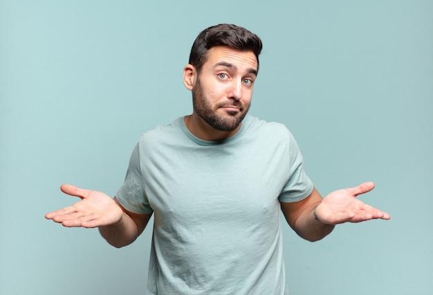 Junger gutaussehender erwachsener mann, der sich verwirrt und verwirrt fühlt, sich über die richtige antwort oder entscheidung nicht sicher ist und versucht, eine wahl zu treffen