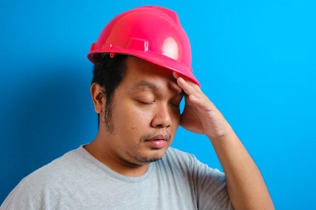 Junger, gutaussehender, fetter asiatischer arbeiter mit grauem t-shirt und sicherheitshelm, der unter kopfschmerzen leidet, verzweifelt und gestresst, weil schmerzen und migräne. hände auf den kopf