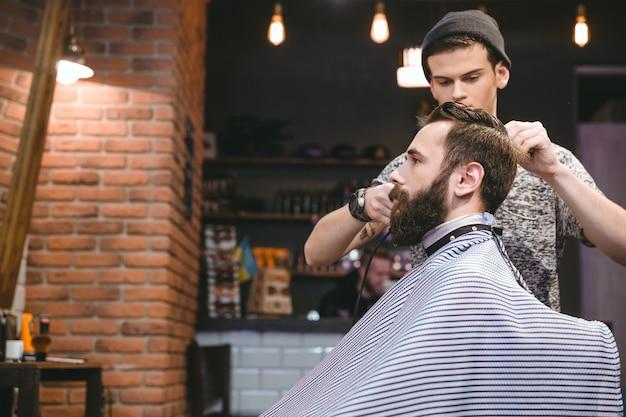 Junger gutaussehender friseur, der einem attraktiven bärtigen mann im schönheitssalon den haarschnitt der männer macht