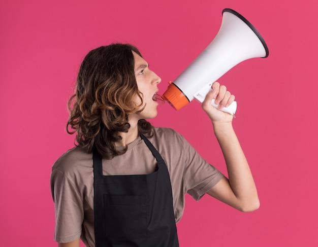 Junger gutaussehender friseur in uniform, der den kopf zur seite dreht und nach oben spricht, indem er von einem lautsprecher isoliert auf einer rosa wand spricht