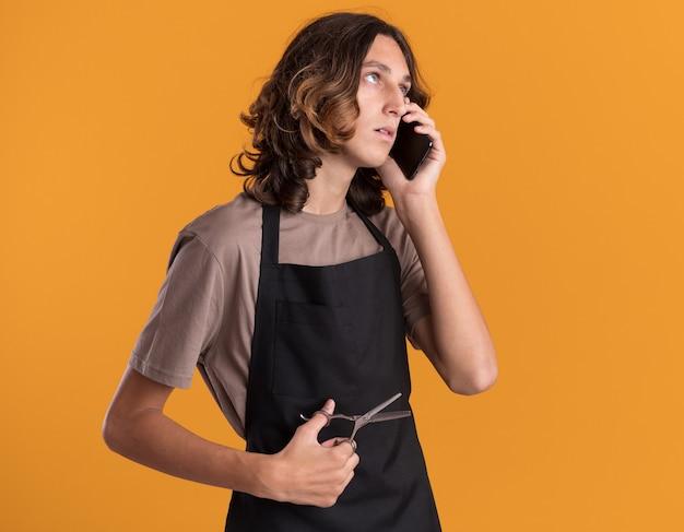 Junger gutaussehender friseur in uniform, der eine schere hält und am telefon spricht, isoliert auf oranger wand mit kopierraum