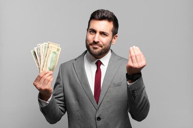 Junger gutaussehender geschäftsmann, der capice oder geldgeste macht und ihnen sagt, dass sie ihre schulden bezahlen sollen!