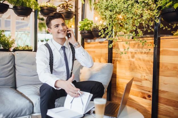Junger gutaussehender geschäftsmann, der ein weißes hemd und eine krawatte trägt, einen laptop arbeitet und ein telefon in einem stilvollen, modernen büro trinkt und latte trinkt