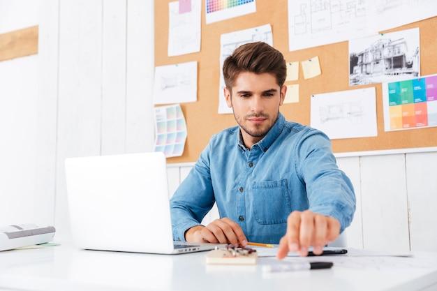 Junger gutaussehender geschäftsmann, der mit laptop im büro arbeitet und im büro stift nimmt