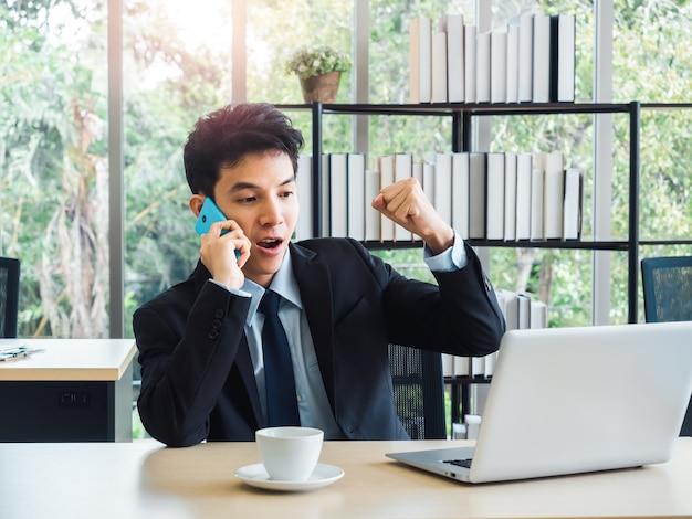 Junger gutaussehender geschäftsmann im anzug, der faust mit aufregendem und schockierendem anhebt, während er mit seinem handy anruft und laptop-schreibtisch auf schreibtisch im büro mit gewinnergefühl und feiern schaut.