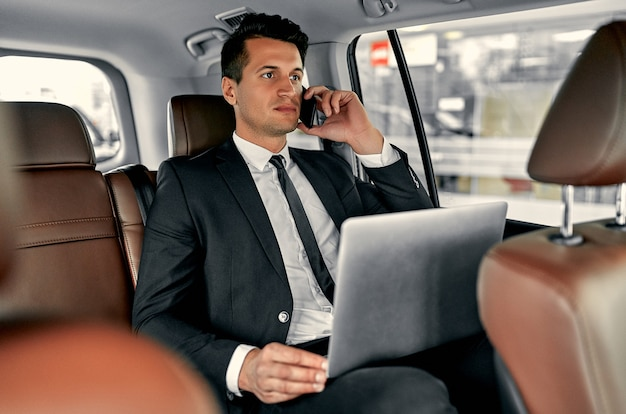 Junger gutaussehender geschäftsmann sitzt im luxusauto. ernsthafter gutaussehender mann im anzug arbeitet mit laptop und spricht auf dem smartphone, während er auf reisen ist.