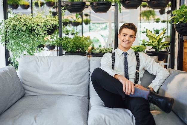 Junger gutaussehender geschäftsmann sitzt in einem büro auf einer sommerterrasse in einem weißen hemd mit hosenträgern und krawatten