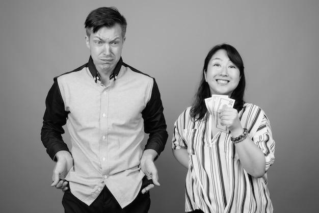 Junger gutaussehender geschäftsmann und reife asiatische geschäftsfrau gegen graue wand