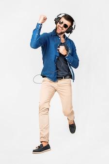 Junger gutaussehender glücklicher lächelnder mann, der musik in kopfhörern tanzt und hört, die auf weißer studiowand lokalisiert werden?