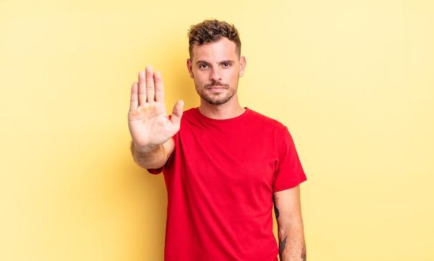 Junger gutaussehender hispanischer mann, der ernst, streng, unzufrieden und wütend aussieht und eine offene handfläche zeigt, die eine stopp-geste macht