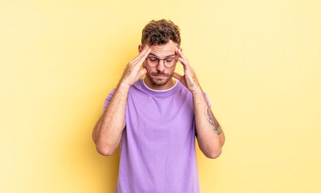 Junger gutaussehender hispanischer mann, der gestresst und frustriert aussieht, unter druck mit kopfschmerzen arbeitet und mit problemen geplagt ist