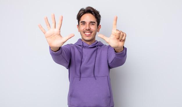 Junger gutaussehender hispanischer mann, der lächelt und freundlich aussieht, nummer sieben oder siebt mit der hand nach vorne zeigt und herunterzählt