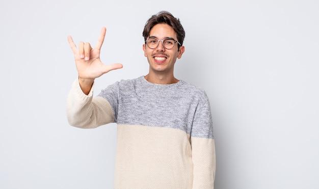Junger gutaussehender hispanischer mann, der sich glücklich, lustig, selbstbewusst, positiv und rebellisch fühlt und mit der hand rock- oder heavy-metal-schilder macht