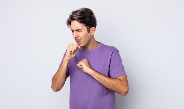 Junger gutaussehender hispanischer mann, der sich mit halsschmerzen und grippesymptomen krank fühlt und mit bedecktem mund hustet