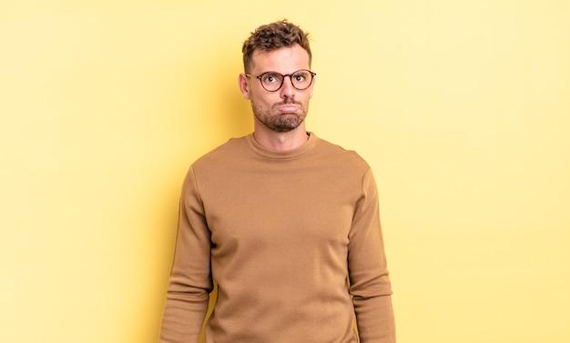 Junger gutaussehender hispanischer mann, der sich traurig und gestresst fühlt, verärgert wegen einer bösen überraschung, mit einem negativen, ängstlichen blick