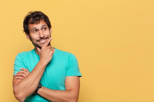 Junger gutaussehender indischer mann. denkender oder zweifelnder ausdruck