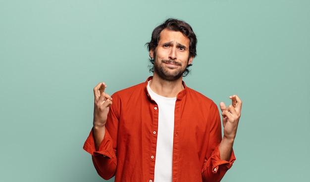 Junger gutaussehender indischer mann, der ängstlich die finger kreuzt und mit einem besorgten blick auf viel glück hofft