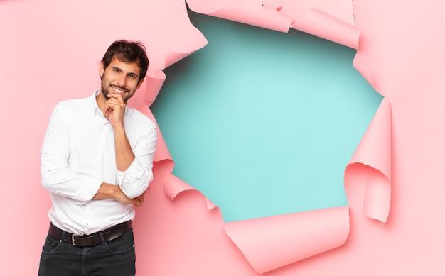 Junger gutaussehender indischer mann, der ausdruck gegen gebrochenen papierlochhintergrund denkt