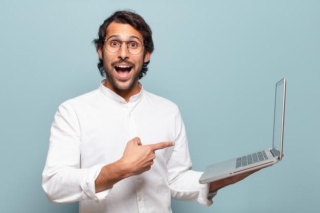 Junger gutaussehender indischer mann, der einen laptop hält.