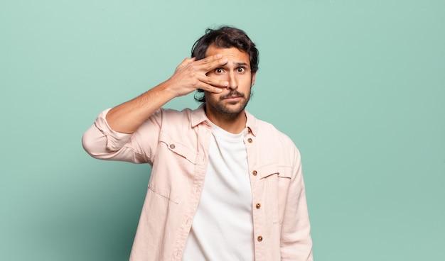 Junger gutaussehender indischer mann, der schockiert, verängstigt oder verängstigt aussieht, das gesicht mit der hand bedeckt und zwischen den fingern späht