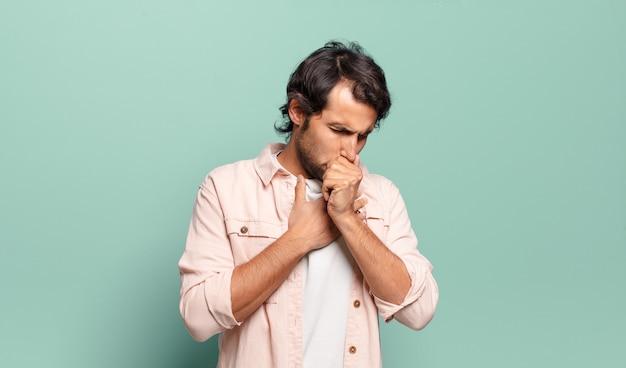 Junger gutaussehender indischer mann, der sich mit halsschmerzen und grippesymptomen krank fühlt und mit bedecktem mund hustet