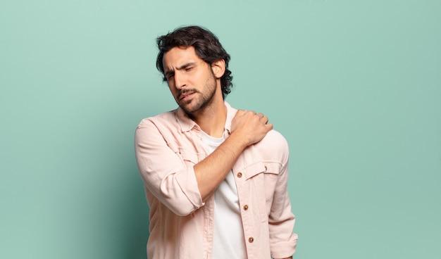 Junger gutaussehender indischer mann, der sich müde, gestresst, ängstlich, frustriert und depressiv fühlt und unter rücken- oder nackenschmerzen leidet