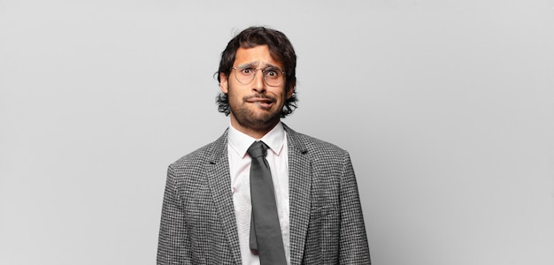 Junger gutaussehender indischer mann, der verwirrt und verwirrt aussieht, mit einer nervösen geste auf die lippe beißt und die antwort auf das problem nicht kennt