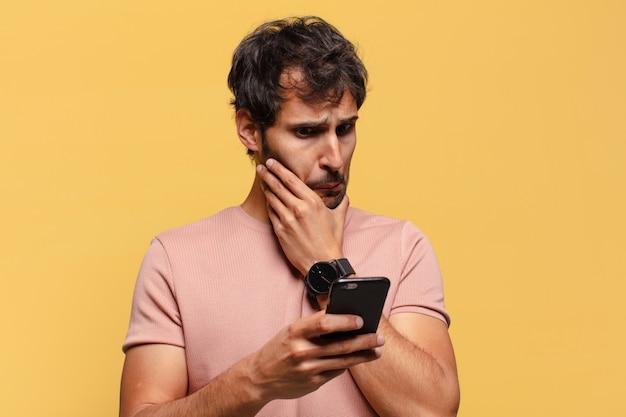 Junger gutaussehender indischer mann hat angst und verwirrt smartphone-konzept