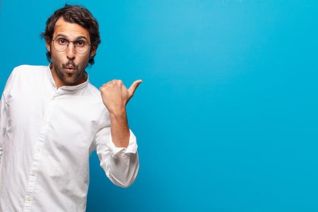Junger gutaussehender indischer mann überrascht oder schockiert ausdruck