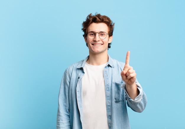 Junger gutaussehender junge, der lächelt und freundlich aussieht, nummer eins oder zuerst mit der hand nach vorne zeigt, herunterzählt