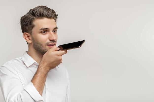Junger gutaussehender kaukasischer mann, der eine sprachnachricht mit dem smartphone über weißem hintergrund aufnimmt