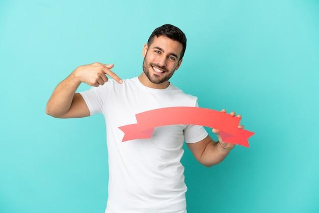 Junger gutaussehender kaukasischer mann isoliert auf blauem hintergrund, der ein leeres plakat hält und darauf zeigt