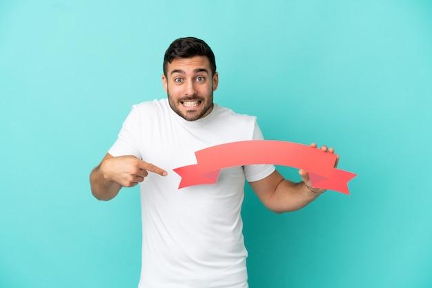 Junger gutaussehender kaukasischer mann isoliert auf blauem hintergrund, der ein leeres plakat mit überraschtem ausdruck hält
