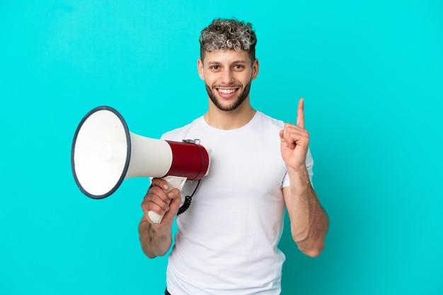 Junger gutaussehender kaukasischer mann isoliert auf blauem hintergrund, der ein megaphon hält und auf eine großartige idee zeigt