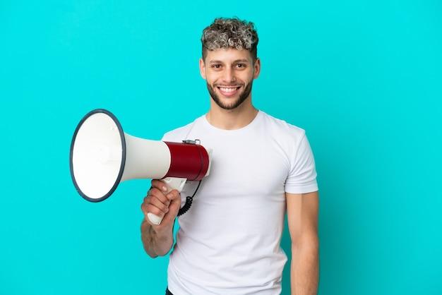 Junger gutaussehender kaukasischer mann isoliert auf blauem hintergrund, der ein megaphon hält und viel lächelt