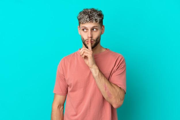 Junger gutaussehender kaukasischer mann isoliert auf blauem hintergrund, der ein zeichen der stille zeigt, geste, die finger in den mund steckt